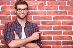 Confident handsome pointing your advertising. Stock Image