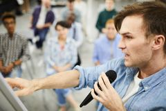 Confident man telling about powerful sales tools. Confident handsome young man in casual shirt pointing at flip chart board and speaking into microphone while stock photography