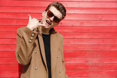 Confident handsome young man in sunglasses showing telephone gesture Stock Photos