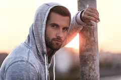 Confident and handsome. Handsome young man wearing hood and looking at camera while standing outdoors stock photo