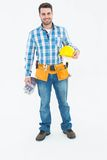 Confident handyman holding hard hat and gloves Stock Photos