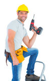 Confident handyman holding power drill while climbing ladder. Portrait of confident handyman holding power drill while climbing ladder on white background Royalty Free Stock Images