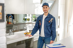 Confident handyman in light cook room stock photography