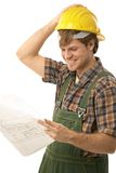 Confident handyman looking at floor plan Royalty Free Stock Images