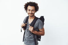 Confident and happy african young man with backpack smiling looking at camera ready to go hitchhiking or just hiking in. Mountains. White background. Copy space stock photography