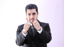 Confident happy arab business man with thumb up. Image of arab businessman wearing black suit and feeling confident with his success and raising thumb up Stock Photos