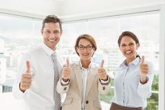Confident happy business people gesturing thumbs up in office Stock Image