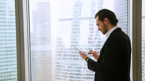 Confident happy businessman standing at office window using tablet smartphone. Confident happy businessman wearing suit standing near big window in office stock footage