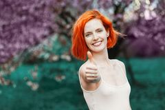 Confident happy female person showing on the outstretched hand a thumb up sign stock image