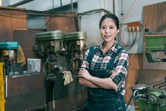 Confident happy lathe factory woman employee. Hands crossed put on chest standing in milling machine department and face to camera smiling royalty free stock images