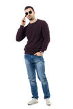 Confident happy man wearing sunglasses talking on the phone looking at camera Royalty Free Stock Photography