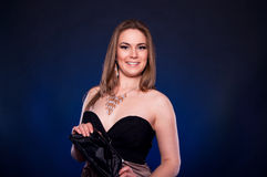Confident happy woman. Happy toothy smiling young blonde female model in cocktail dress holding her small black purse and looking at camera against black and Stock Images