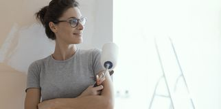 Confident happy woman painting walls at home. Confident smiling woman posing with a paint roller and looking away: home renovation and redecoration concept stock images