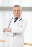 Confident healthcare professional. Confident mature doctor stand Royalty Free Stock Image