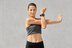Confident healthy woman with appealing look, does exercises, stretches hands, wears casual top, smartwatch for controlling her hea. Lth, over grey concrete wall stock image