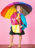 Confident in her fall garments. Waterproof accessories manufacture. Kid girl happy hold colorful umbrella wear. Waterproof cloak. Waterproof accessories make royalty free stock photography
