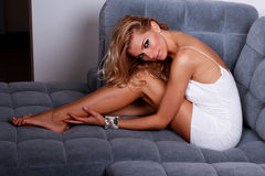 Confident in her white dress. Sensual fashion female model in white dress lying on the sofa Royalty Free Stock Images