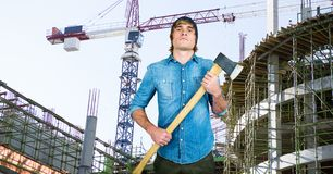 Confident hipster holding ax against incomplete buildings Royalty Free Stock Images