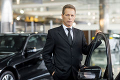 Confident in his choice. Confident grey hair man in formalwear holding hand on opened car door and looking at camera Royalty Free Stock Photography