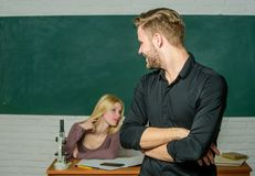 Confident in his knowledge. Handsome man standing hands crossed in classroom with teacher. Male student with examiner at royalty free stock image