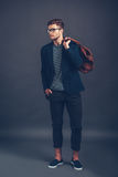 Confident in his style. Full length of confident young handsome man in glasses holding bag and looking away while standing against grey background Royalty Free Stock Photos
