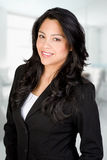 Confident Hispanic Businesswoman. Wearing a Dark Suit in Office Setting Stock Image