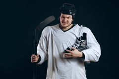 Confident hockey player looking at camera with skate in hand. Isolated on black. royalty free stock photo