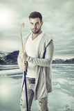 Confident hokey player with the caman. Young athlete with the caman standing on the background of iced mountain lake stock images
