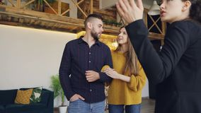 Confident housing agent is showing spacious modern house with beautiful interior to happy young couple, people are. Confident housing agent is showing spacious stock video footage