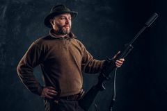 Confident hunter posing with a rifle and looking sideways. Studio photo against dark wall background royalty free stock photo