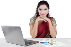 Confident indian businesswoman smiling at camera. Portrait of indian young businesswoman smiling at the camera while wearing traditional clothes with laptop and Royalty Free Stock Images