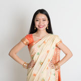 Confident Indian girl in sari smiling. Portrait of confident Indian girl in sari smiling over grey background Stock Photography