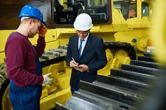 Giving tour of modern factory. Confident inspector in suit and hardhat taking necessary notes while young bred-haired technician giving tour of modern heavy Stock Photos