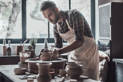 Confident and inspired potter. Confident young man making ceramic pot on the pottery wheel Stock Photos