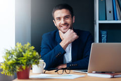 Confident and inspired. Confident young man holding hand on chin and smiling while sitting at his working place in office Royalty Free Stock Images