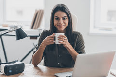 Confident and inspired. Confident young woman in smart casual wear holding coffee cup and looking at camera with smile while sitting at her working place in Stock Photos