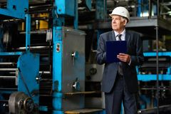 Confident Investor at Modern Plant. Senior investor in suit and protective helmet taking necessary notes in clipboard while walking along production department Stock Image