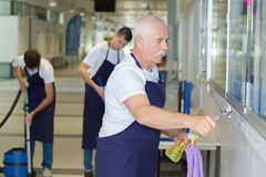 Confident janitors at work senior employee in foreground Stock Image
