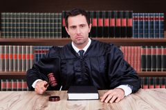 Confident judge striking gavel in courtroom Stock Image