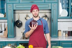 Confident at kitchen. Take old favorites and make healthful substitutions. Take favorite recipes and lighten them up. Man handsome chef holds violet cabbage royalty free stock photography