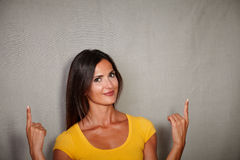 Confident lady pointing up while looking at camera Royalty Free Stock Image