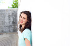 Confident lady smiling leaning against white wall Royalty Free Stock Image