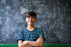 Confident Latino Boy Smiling At Camera During Math Lesson. Concept on blackboard at school. Young people, student and pupil in classroom. Smart hispanic boy stock images