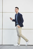 Confident laughing business man walking with smart phone Stock Photography