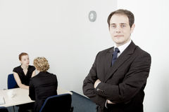 Confident leader or manager. Confident handsome young male leader, or manager, standing with his arms folded smiling at the camera, while his team go about their Stock Images