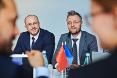 Confident leaders. Two confident leaders listening to talk of their foreign colleagues royalty free stock photo