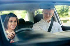 Confident learner driver. Learner driver student driving car with instuctor. happy and confident smiling girl Royalty Free Stock Image