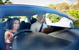 Confident learner driver. Learner driver student driving car with instructor. happy and confident smiling girl Stock Images