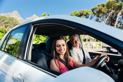 Confident learner driver. Learner driver student driving car with instructor. happy and confident smiling girl stock photography