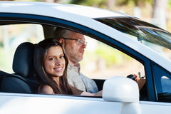 Confident learner driver. Learner driver student driving car with instructor. happy and confident smiling girl royalty free stock photos